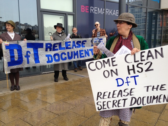 Sherlock Holmes searches for secret HS2 documents at rail summit in Hastings, watched by Miss Marple, Inspector Poirot and Kojak. 31 Mar 2014 (credit: Combe Haven Defenders)