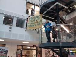 Local resident holds banner as Amber Rudd opens jobs fair, Sussex Coast College Hastings, 26 February 2016